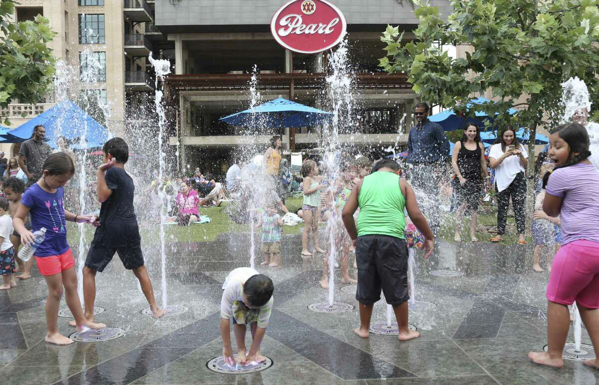 One way to beat the heat: Children play in a fountain at the Pearl Park on July 12, 2017.