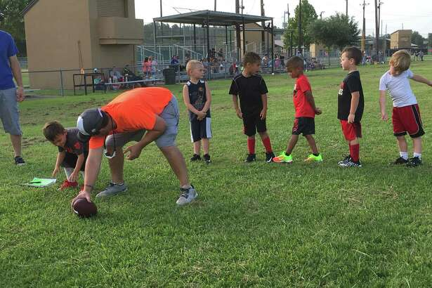 The Mighty Mights, the four-year-old division of the Huffman Youth Athletic Association football league, take turns working on an off-the-ball drill during tryouts at the football field at I.T. May Park on July 25