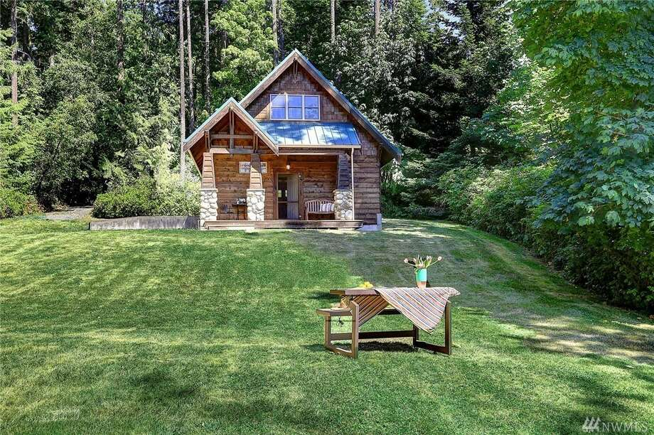 This home on Camano Island is listed for $545,000.The cabin has two bedrooms and one bathroom, and has a beautiful log-cabin exterior. It's on the east side of the island and looks out over Port Susan. The home sits on 1.2 acres.You can see the full listing here. Photo: Photos By Ian Gleadle/listing Courtesy Kimberley Thomas, Realogics Sotheby's International Realty
