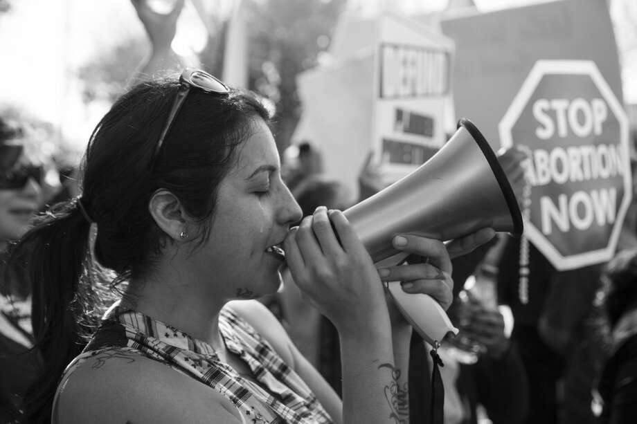 Mercedes Soto cries as she sings a hymn into a megaphone while she and more than a thousand other anti-abortion protestors face off with abortion rights advocates. Photo: Carolyn Van Houten
