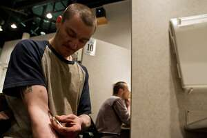 A client of the Insite supervised injection Center in Vancouver, Canada, injects himself on May 3, 2011.