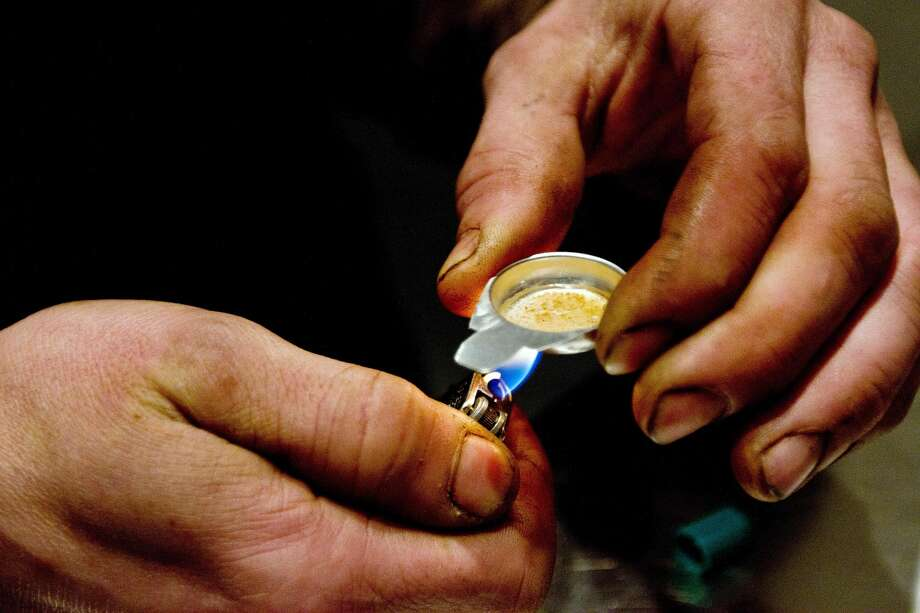 A client of the Insite supervised injection Center in Vancouver, Canada, prepares a dose of drug to inject on May 3, 2011. Photo: AFP/AFP/Getty Images