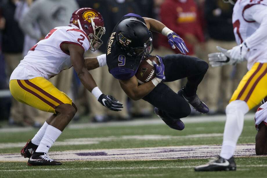 Washington Huskies running back Myles Gaskin flies through the air before he is stopped by USC Trojans defensive back Adoree' Jackson in the first half of a football game at Husky Stadium on Saturday, Nov. 12, 2016. (GRANT HINDSLEY, seattlepi.com) Photo: GRANT HINDSLEY, SEATTLEPI.COM