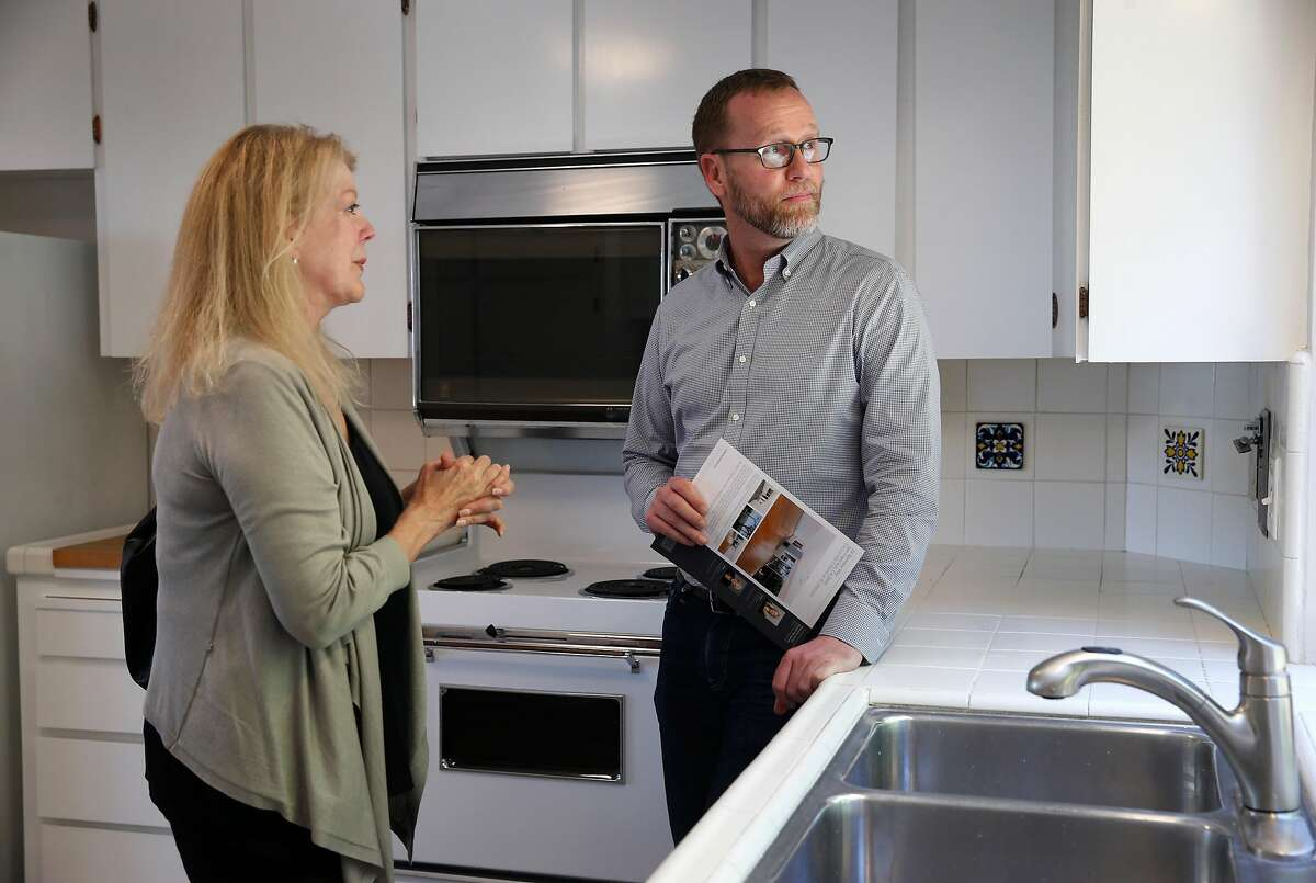 Real estate agents Marsha Williams and Judson Gregory tour a single-family home for sale on Berkeley Way in the Diamond Heights neighborhood at an open house for brokers in San Francisco, Calif. on Tuesday, July 25, 2017.