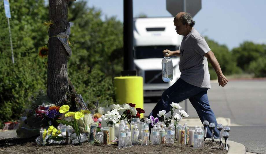 A man delivers a large bottle of water to a make-shift memorial Wednesday, July 26, 2017, in the parking lot of a Walmart store near the site where authorities Sunday discovered a tractor-trailer packed with immigrants outside a Walmart, in San Antonio. Several people died and others hospitalized after being crammed into a sweltering tractor-trailer in the midsummer Texas heat in what authorities describe as an immigrant-smuggling attempt gone wrong. (AP Photo/Eric Gay) Photo: Eric Gay, STF / Associated Press / Copyright 2017 The Associated Press. All rights reserved.