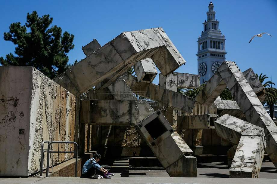 Tiffany Parker hangs out by the Vaillancourt Fountain on Justin Herman Plaza at the foot of Market Street. Supervisor Aaron Peskin suggests temporarily renaming it Embarcadero Plaza. Photo: Gabrielle Lurie, The Chronicle