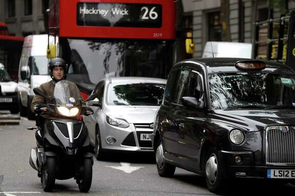 Vehicles pass by in central London. Britain says it will ban the sale of new cars and vans using diesel and gasoline starting in 2040 as part of a sweeping plan to tackle air pollution.