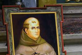 FILE - In this May 6, 2015 file photo, a painting of Rev. Junipero Serra is seen above his grave inside the basilica at the Carmel Mission in Carmel, Calif. Pope Francis� apology for the Roman Catholic Church�s crimes against indigenous peoples has not softened opposition among some California Native Americans to his decision to canonize 18th-century Franciscan missionary Junipero Serra, extolled by the Vatican as a great evangelizer, but denounced by some tribal officials as a destroyer of Native culture.(David Royal/The Monterey County Herald via AP, File) MANDATORY CREDIT