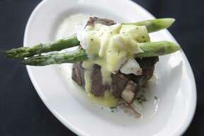 Bone-in beef tenderloin filet served in the classic Oscar style with lump crab and asparagus at Myron's Prime Steakhouse.