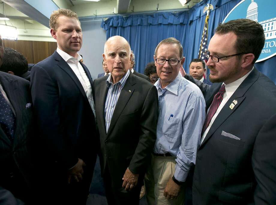 Gov. Jerry Brown, center left, flanked by Republicans Chad Mayes, of Yucca Valley, left, Tom Berryhill, center right, of Twain Harte, and Devon Mathis, of Visalia, right, leaves a news conference after the Legislature approved a pair of climate change bills. Brown got Republican support for the measure, which will extend the state's cap-and-trade program, but the deal may threaten the governor's bullet train. Photo: Rich Pedroncelli, Associated Press