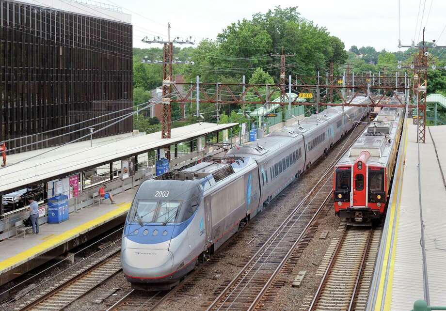 The Amtrak Acela Express, at left, heading toward New York City, passes through the Greenwich train station. Photo: Bob Luckey Jr. / Hearst Connecticut Media / Greenwich Time