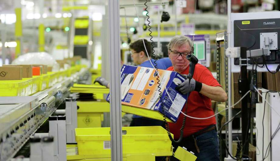 FILE - In this Monday, Nov. 30, 2015, file photo, Mark Oldenburg processes outgoing orders at Amazon.com's fulfillment center in DuPont, Wash. On Wednesday, July 26, 2017, Amazon said that it's looking to fill more than 50,000 positions across its U.S. fulfillment network. It's planning to make thousands of job offers on the spot during its first Jobs Day on Aug. 2, where potential employees will have a chance to see what it's like to work at Amazon by visiting one of 10 participating fulfillment centers. (AP Photo/Ted S. Warren, File) Photo: Ted S. Warren, STF / Copyright 2016 The Associated Press. All rights reserved. This material may not be published, broadcast, rewritten or redistribu