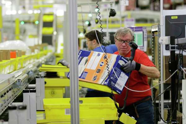 FILE - In this Monday, Nov. 30, 2015, file photo, Mark Oldenburg processes outgoing orders at Amazon.com's fulfillment center in DuPont, Wash. On Wednesday, July 26, 2017, Amazon said that it's looking to fill more than 50,000 positions across its U.S. fulfillment network. It's planning to make thousands of job offers on the spot during its first Jobs Day on Aug. 2, where potential employees will have a chance to see what it's like to work at Amazon by visiting one of 10 participating fulfillment centers. (AP Photo/Ted S. Warren, File)