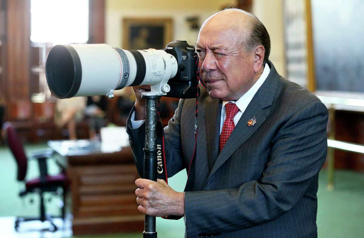 Sen. Juan Hinojosa, D-McAllen, commandeers a camera from photographer Marjorie Cotera to take pictures of his colleagues on the floor during Wednesday's debate over local issues at the Capitol in Austin.