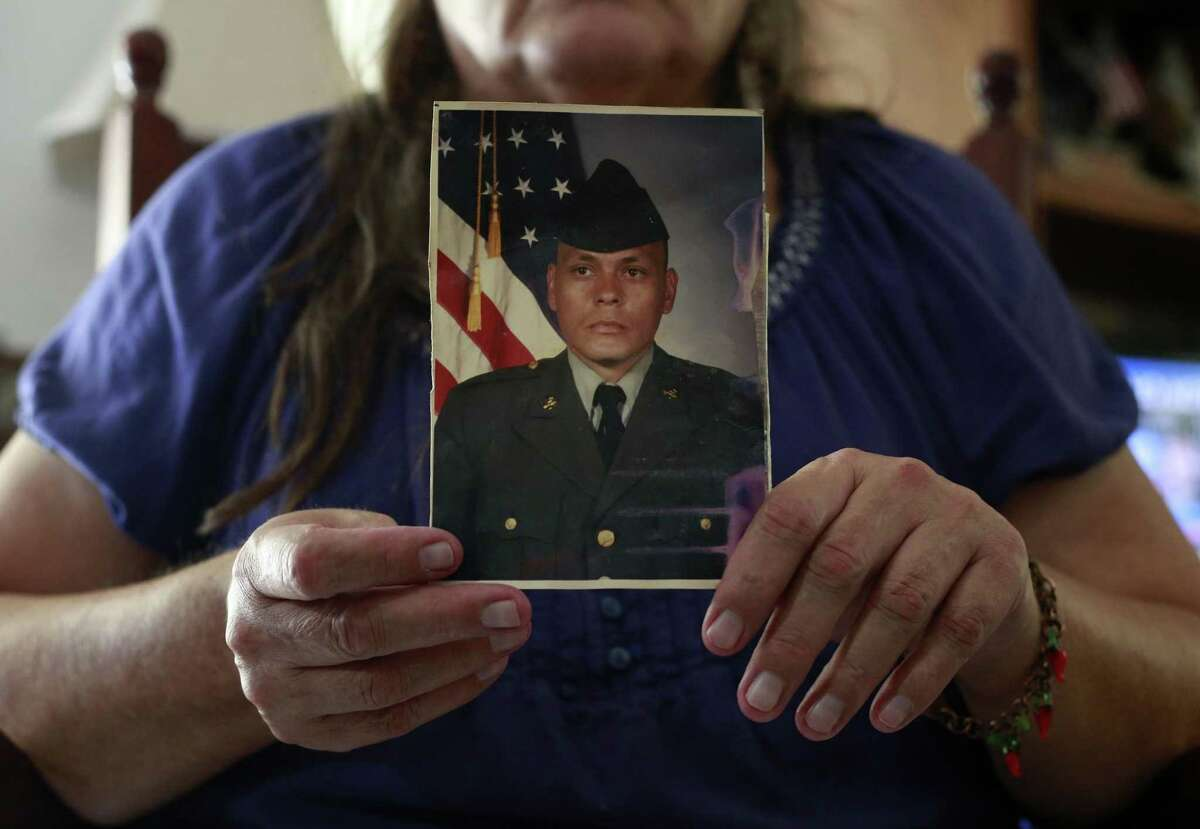 Daniel Pons, 64, holds a picture of herself in her days in the Army Reserve.