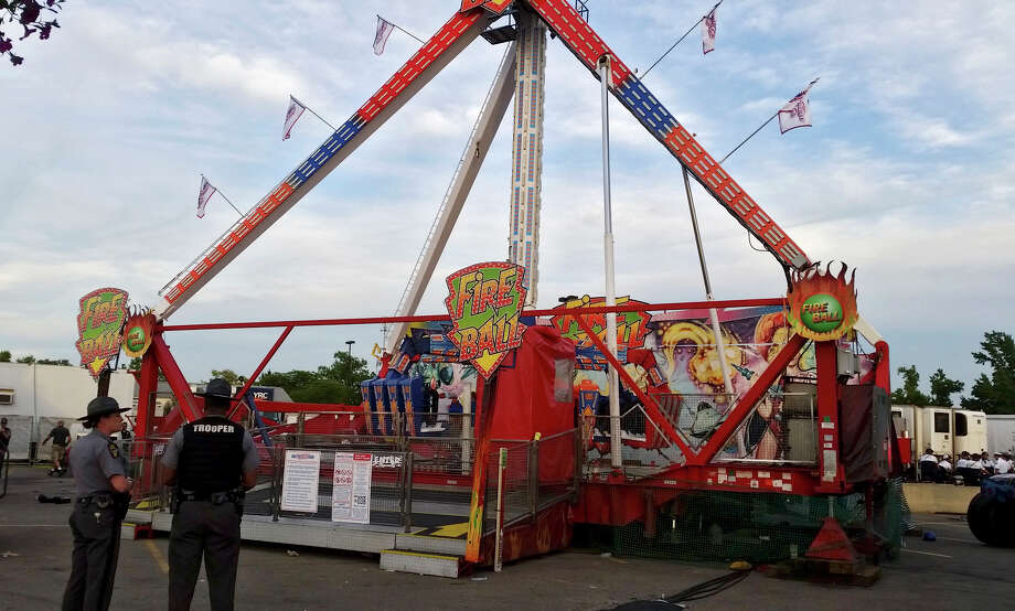 Authorities stand near the Fire Ball amusement ride after the ride malfunctioned injuring several at the Ohio State Fair, Wednesday, July 26, 2017, in Columbus, Ohio. Some of the victims were thrown from the ride when it malfunctioned Wednesday night, said Columbus Battalion Chief Steve Martin. (Jim Woods/The Columbus Dispatch via AP) Photo: Jim Woods, AP / 2017 The Columbus Dispatch