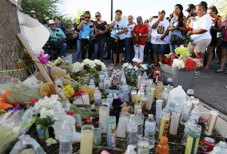 A memorial created for the victims of a smuggling venture turned deadly early Sunday continued growing Wednesday as area residents left water, food and candles for the deceased on the South Side. Over 50 mourners gathered at the site at the Walmart located on the southside of town and recited the Rosary while holding candles and flowers. Some cried and choked back tears as the vigil concluded. Flowers were placed atop of the memorial as a parting farewell for the victims. (Kin Man Hui/San Antonio Express-News)