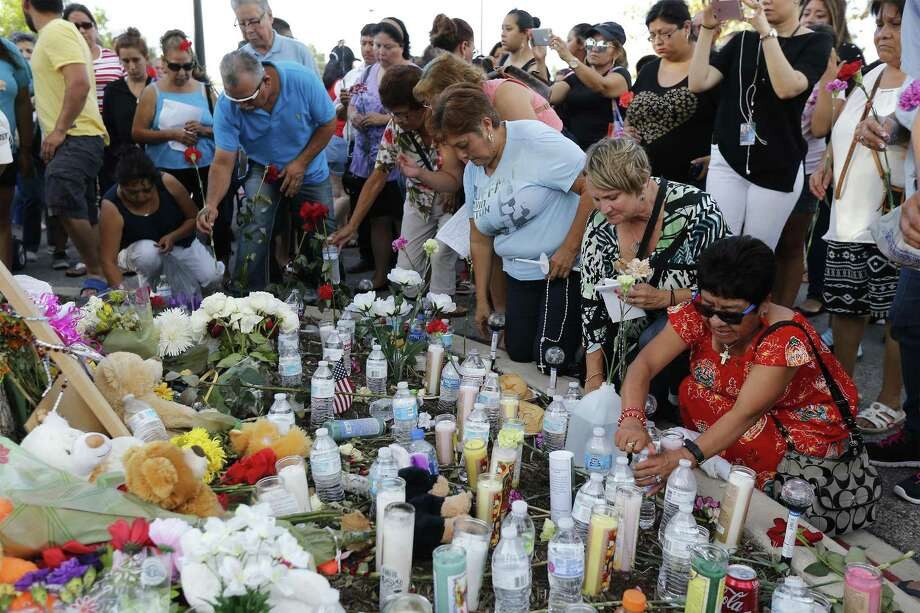 Area residents left water, food and candles at a memorial created for the victims of a smuggling venture turned deadly recently. More than 50 mourners gathered at the site at the Walmart located on the southside of town and recited the rosary while holding candles and flowers. Photo: Kin Man Hui /San Antonio Express-News / ©2017 San Antonio Express-News