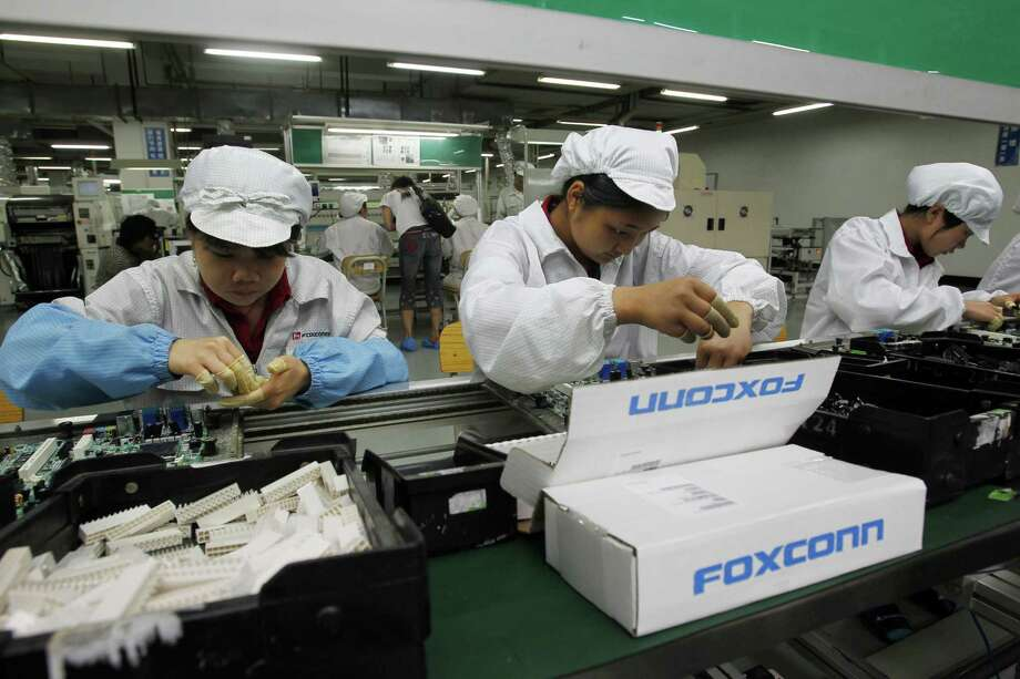 Employees work on the production line at the Foxconn complex in the Chinese city of Shenzhen.  Photo: Kin Cheung, STF / Copyright 2017 The Associated Press. All rights reserved.