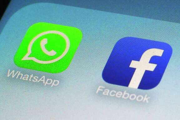 FILE - This Feb. 19, 2014, file photo, shows WhatsApp and Facebook app icons on a smartphone in New York. Facebook has squeezed just about as many ads into its main platform as it can. Any more and users might start to complain. Now, ads are moving on to Messenger, and WhatsApp may not be too far behind. (AP Photo/Patrick Sison, File)