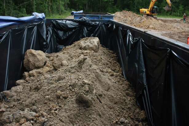 A dumpster skid fills up with the illegally dumped municipal waste AC-10 asphalt buried by Pct. 3 workers under the orders of former Pct. 3 Commissioner Eddie Lowery. The site has been remediated, but the Texas Commission on Environmental Quality wants additional samples to prove that it has been cleared.
