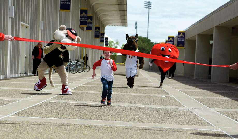 Ryan Galvin, 6, races mascots, SouthPaw of the ValleyCats, Damien, the Great Dane of UAlbany and Ticker of the American Heart Association during the American Heart Association Torch Ceremony of the Capital Region Heart Walk Run on Thursday, May 11, 2017, at the University at Albany in Albany, N.Y.  This years Torch Ceremony honored Jonathan Kirk who received a heart transplant in 2015 and passed away on January 13, 2017.  The Capital Region Heart Walk Run will be held on June 3rd at the University at Albany and this year the event will include a 5K run.  People can register for the event at http://www.CapitalRegionHeartWalk.org.  (Paul Buckowski / Times Union) Photo: PAUL BUCKOWSKI / 20040488A