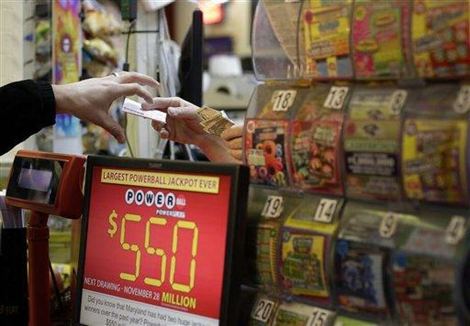 A customer, left, reaches for a Powerball ticket that he purchased Wednesday in a convenience store in Baltimore. A Connecticut Lottery official says three winning tickets worth at least $1 million each were sold in Connecticut as part of the $579.9 million Powerball jackpot as the big prize went to winners in Arizona and Missouri. Associated Press Photo: ASSOCIATED PRESS / AP2012