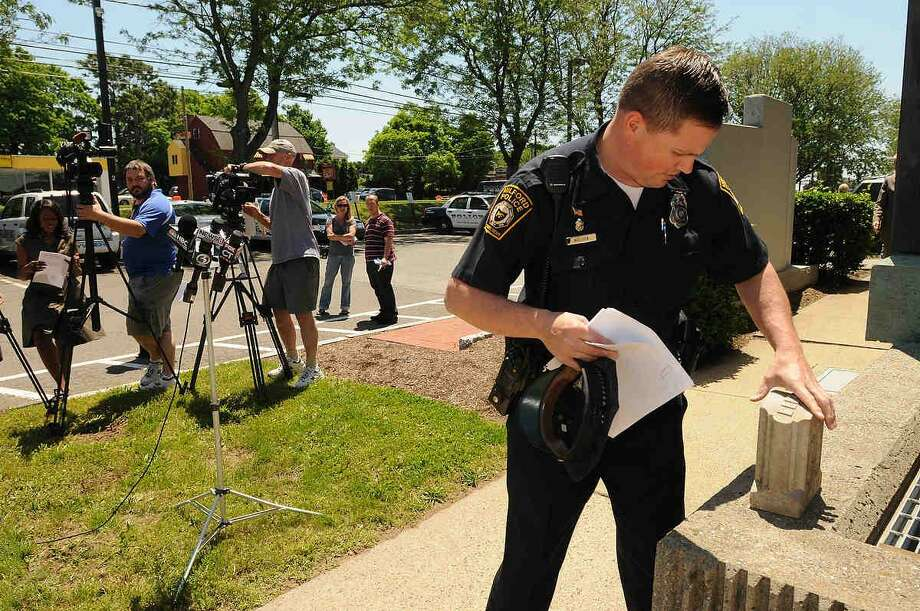 Milford Police Officer Jeffrey Nielson places the headstone belonging to baby Bertha, found in Milford in 1977, before the start of a press conference Thursday at police headquarters announcing its return to Chelsea, Mass. Members of the Milford Police Department and a person familiar with genealogy research were able to locate death record in Chelsea Mass., for the name inscribed on the gravestone.  Peter Hvizdak/Register Photo: New Haven Register / ©Peter Hvizdak /  New Haven Register