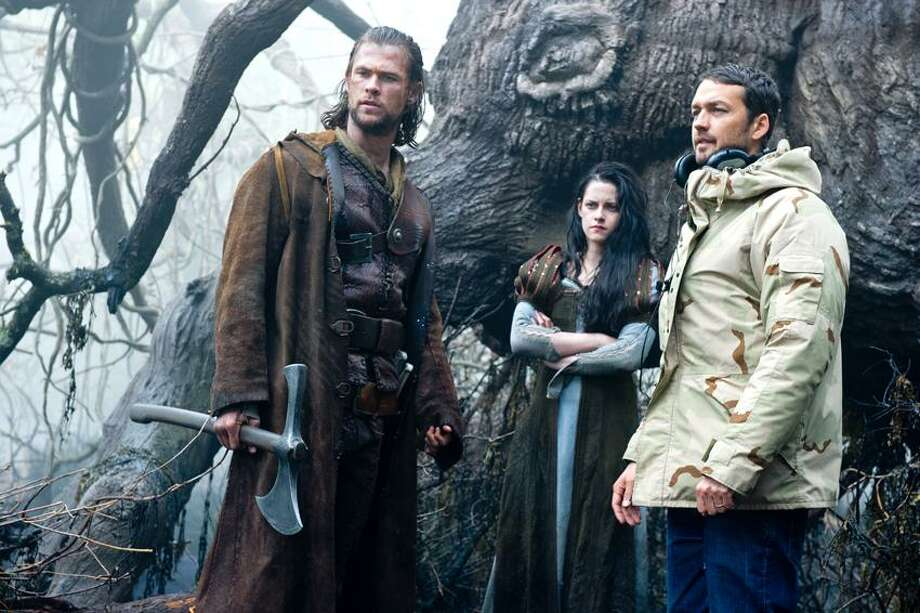 """Alex Bailey/Universal Pictures photo: Chris Hemsworth, left, and Kristen Stewart work with director Rupert Sanders on the set of """"Snow White and the Huntsman."""" Photo: AP / Copyright: © 2012 Universal Studios. ALL RIGHTS RESERVED."""