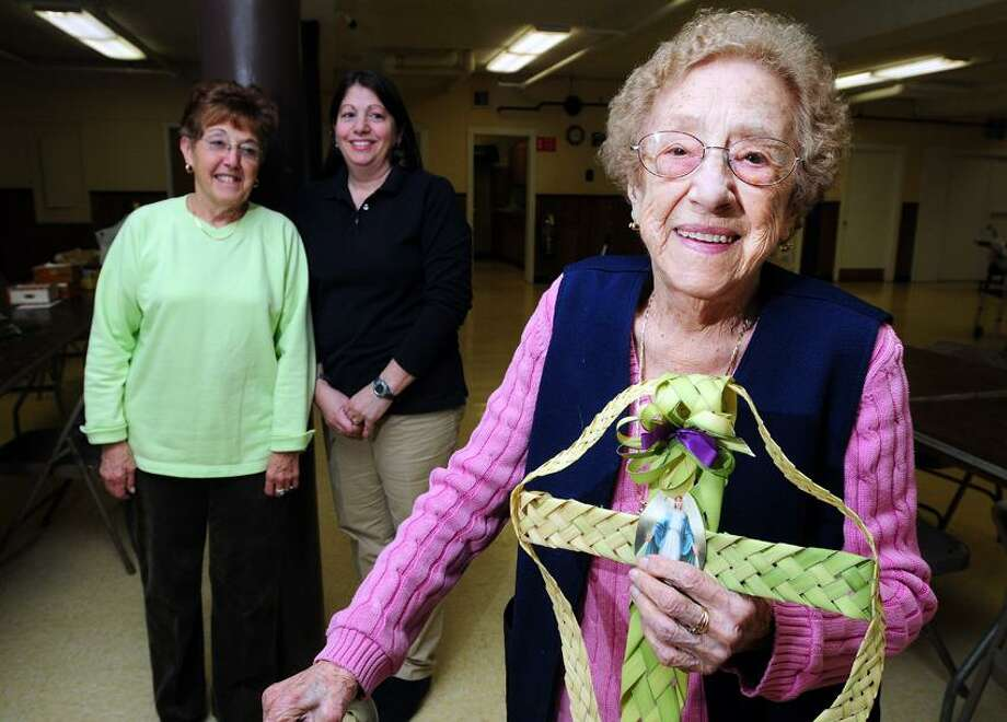 Ninety-eight year old Mary Altieri (right) is photographed holding a palm frond cross in the basement of St.Francis Church in New Haven on 3/30/2012.  In the background is Louise Giammattei (left) and Olga-Lynn D'Ambrosca (center).Photo by Arnold Gold/New Haven Register   AG0445A