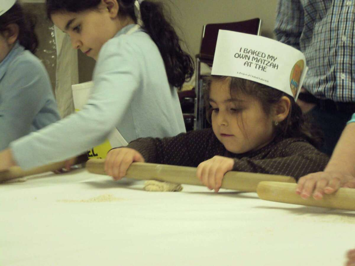 RICKY CAMPBELL/Register Citizen Children learn to roll matzah dough during Chabad Lubavitch's recent workshop in Litchfield.