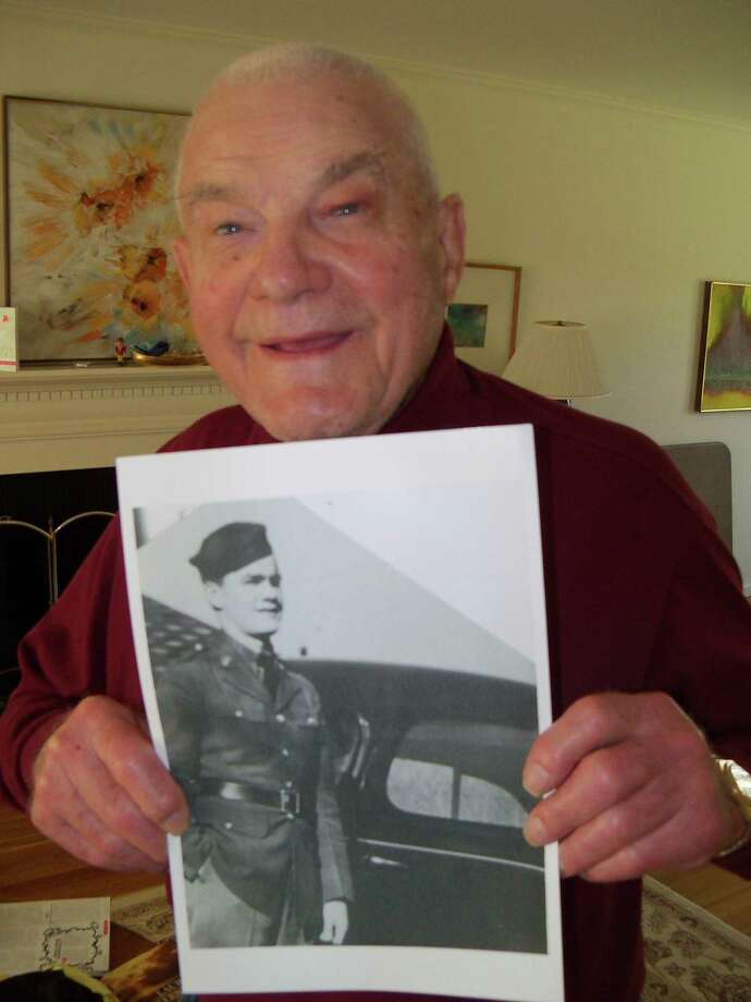 SCOT ALLYN/Register Citizen Dan Crowley, 89, of Simsbury, holds a photo of himself at 18 when he joined the Army and was shipped off to the Phillipines to fight. He was a POW after the fall of Bataan, and was held by the Japanese for 42 months. The Bataan Death March will be memorialized during a program in Simsbury on April 9.