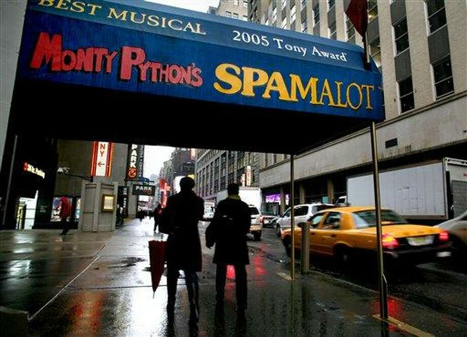 """In this 2008 file photo, pedestrians walk under the marquee of the Broadway show """"Monty Python's Spamalot"""" at the Shubert Theatre in New York. A producer of the film """"Monty Python and the Holy Grail"""" is suing the comedy troupe over royalties from the hit stage musical """"Spamalot."""" Producer Mark Forstater wants a bigger share of proceeds from the show, which is based on the 1975 movie spoof of the legend of King Arthur. Python members Eric Idle, Michael Palin and Terry Jones are to give evidence during a five-day hearing that began Friday, at London's High Court. ASSOCIATED PRESS PHOTO/Craig Ruttle, File Photo: AP / FR61802 AP"""