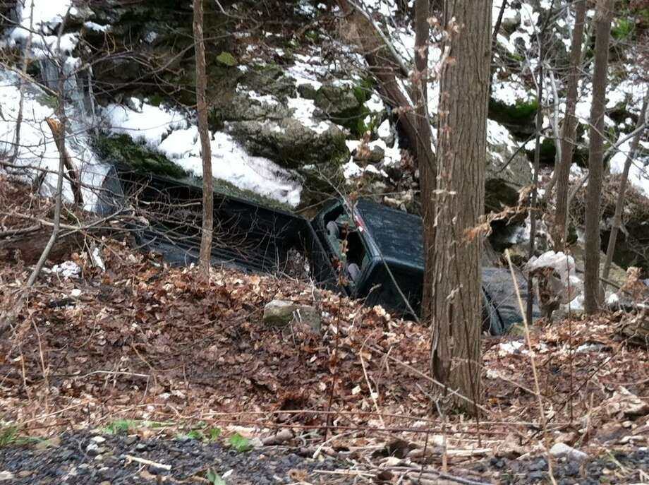 Photo by CAITLIN TRAYNOR A truck rests in the ravine off Mosquito Point Road in Munnsville following an apparent suicide attempt.