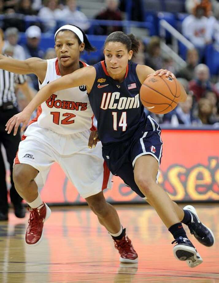 Connecticut's Bria Hartley, right, drives past St. John's Briana Brown during the first half Connecticut's 74-43 victory in an NCAA college basketball game in the semifinals of the Big East women's tournament in Hartford, Conn., Monday, March 5, 2012. (AP Photo/Fred Beckham) Photo: AP / AP2012