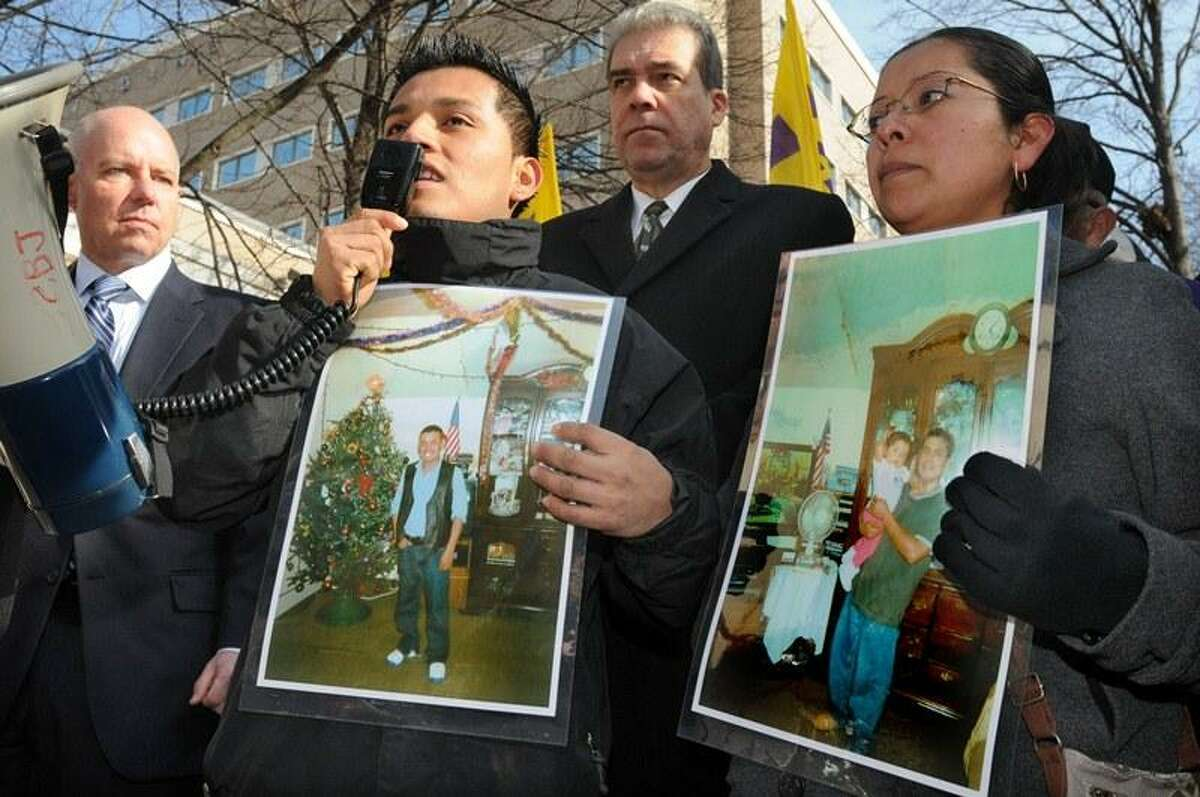 Immigration-policy protestors gathered in a small plaza near the Ribicoff Federal Building in Hartford. Under Secretary for Criminal Justice Policy and Planning Michael Lawlor rear left, and State Rep.-elect Edwin Vargas (Hartford), rear right, were in attendance. Josemaria Islas' brother Paulino Francisco front left, and sister Juana Islas right, both of New Haven, speak about their brother's detention while holding photos of him. Mara Lavitt/New Haven Register 11/29/12