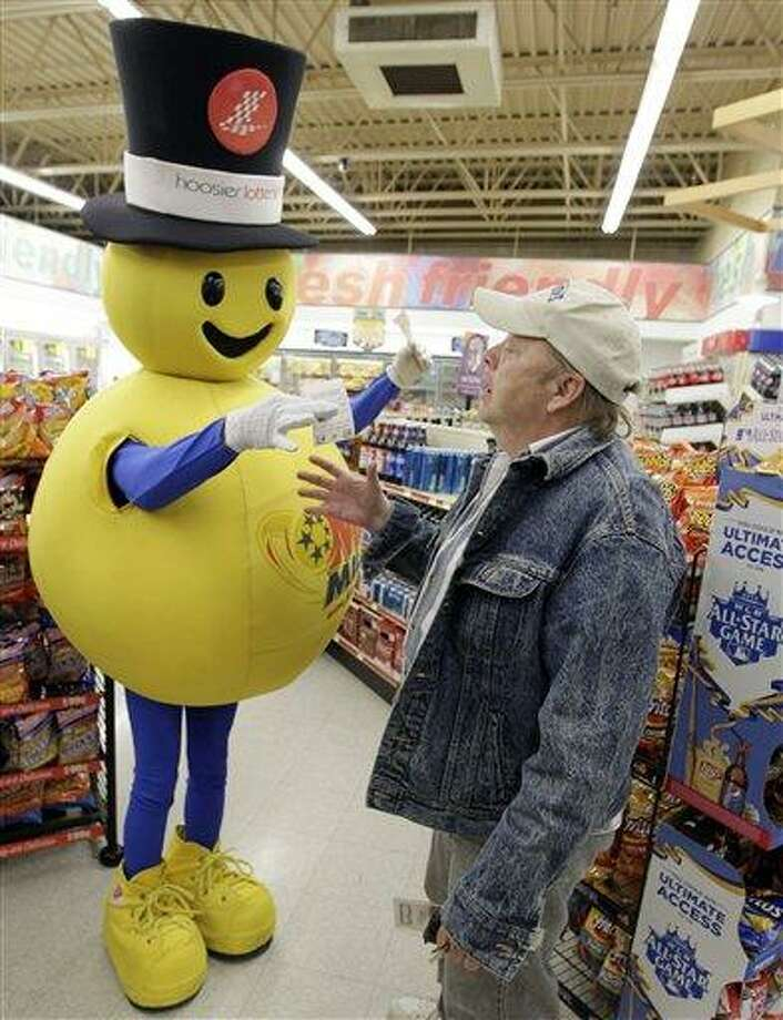 Tom Coombs receives a free Mega Millions Lottery ticket from the mascot at a store in Zionsville, Ind., Friday. The Mega Millions Lottery jackpot has reached a record $540 million. Associated Press Photo: AP / AP