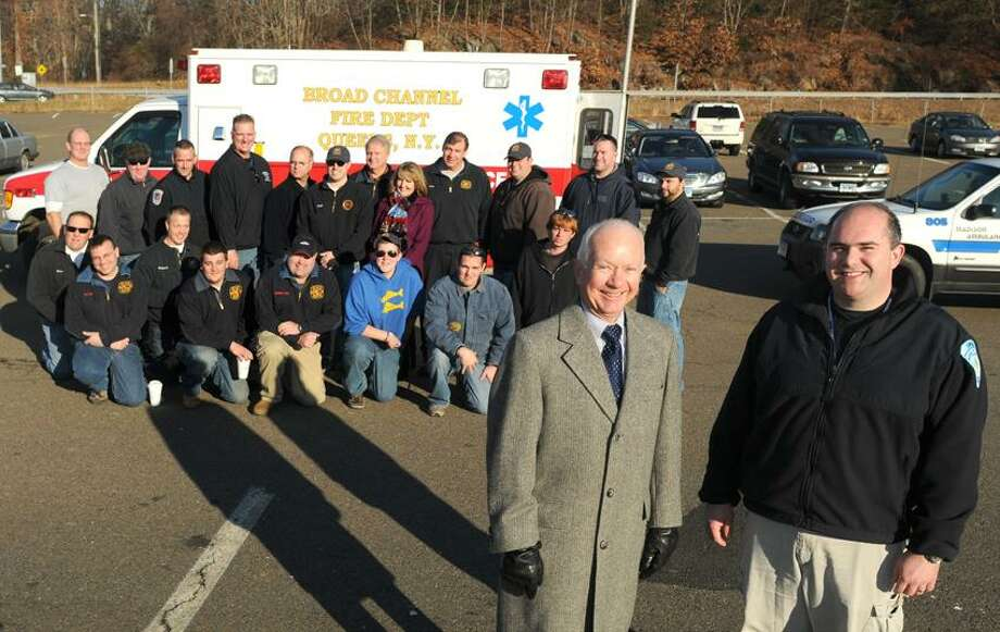 Meeting in the I-95 commuter parking lot in Madison, Connecticut before driving a caravan to Broad Channel N.Y. Volunteer Fire Department, Madison First Selectman Fillmore McPherson, left front,  and  Christopher Bernier, EMS Director of the Madison Ambulance Association, right front,  with members of the North Madison Volunteer Fire Department, the Madison Hose Company and the Madison Ambulance Association, rear in photo,  stand in front of a 1998 Ford Ambulance  that will be donated by Madison to the Broad Channel Volunteer Fire Department Thursday, November 29, 2012.The Broad Channel Volunteer Fire Department  lost most of their equipment and emergency vehicles due to Hurricane Sandy. The caravan includes other Madison emergency vehicle with trailers containing other helpful donations by Madison for the Town of Broad Channel. Thursday, November 29, 2012    Photo by Peter Hvizdak / New Haven Register Photo: New Haven Register / ©Peter Hvizdak /  New Haven Register