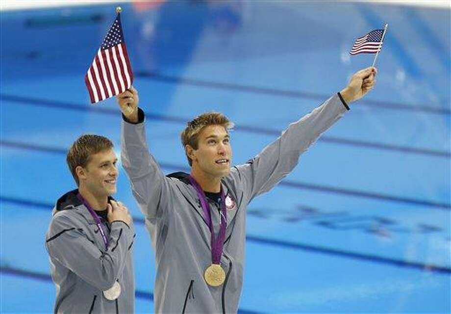 United States' gold medalist Matthew Grevers waves American flags as he walks with his teammate and silver medalist Nick Thoman at the Aquatics Centre after their medal ceremony for the the men's 100-meter backstroke swimming final during the 2012 Summer Olympics in London, Monday, July 30, 2012. (AP Photo/Daniel Ochoa De Olza) Photo: AP / AP
