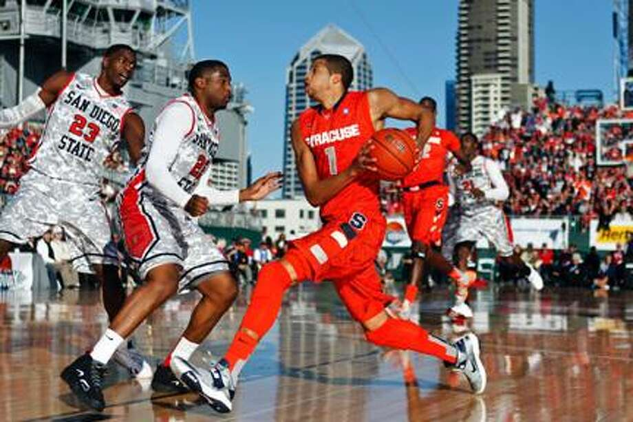 AP Photo Syracuse's Michael Carter-Williams drives against San Diego State's Chase Tapley, center, and Deshawn Stephens during their season opener. Carter-Williams has been a leader for the Orange, averaging over 10 points and nearly 10 assists per game. Photo: ASSOCIATED PRESS / AP2012