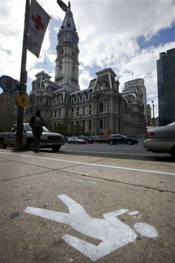"""FILE - An April 2, 2012 file photo shows an """"e-lane"""" sidewalk graphic displayed in view of City Hall, in Philadelphia. Philadelphia Mayor Michael Nutter used April Fool's Day to have a little fun with what he says is a real problem: distracted walking. City officials painted lines and oblivious stick-figure pictures on one stretch of John F. Kennedy Boulevard near City Hall as a jab at pedestrians who keep their eyes on their cellphone screens and not their surroundings. Across the country on city streets, in suburban parking lots and in shopping centers, there is usually someone strolling while talking on a phone, texting with their head down, listening to music, or playing a video game. The problem isn't as widely discussed as distracted driving, but the danger is real.  (AP Photo/Matt Rourke, File) Photo: AP / AP"""