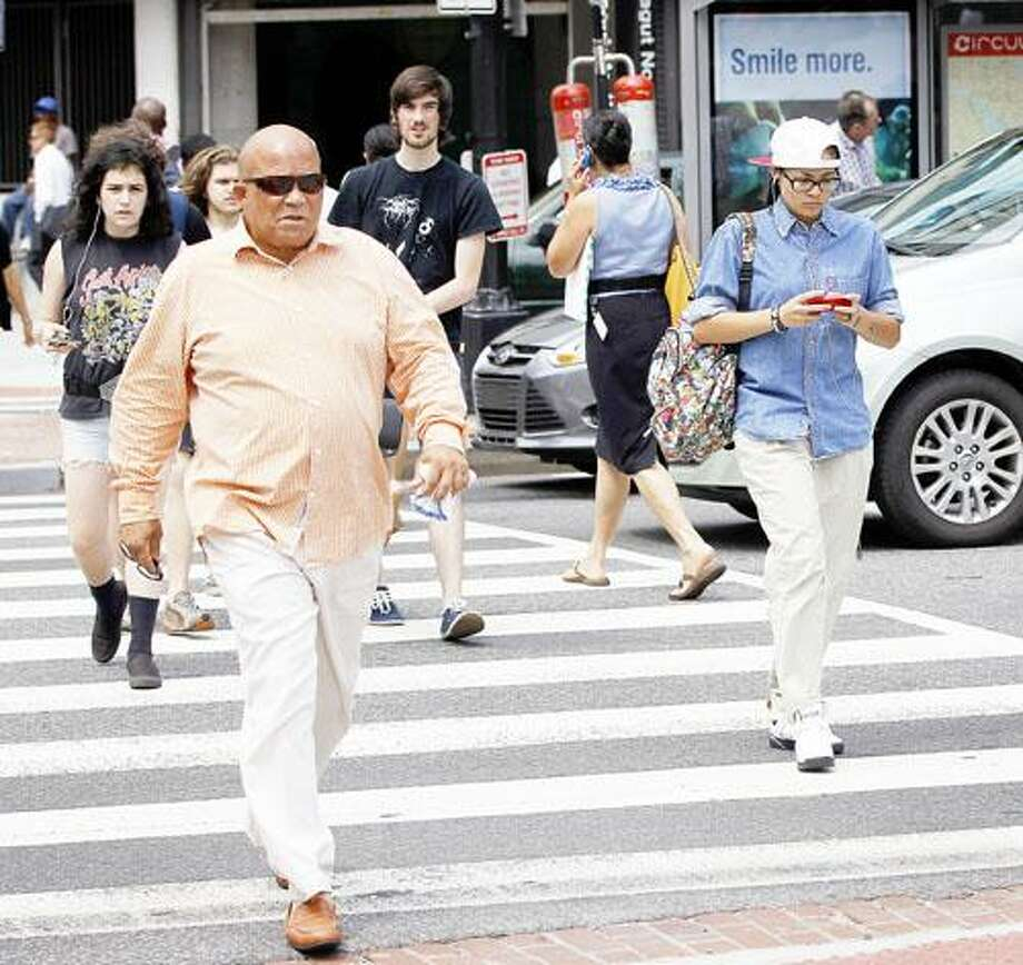 In this photo taken July 10, 2012, Pedestrians cross K Street and Connecticut Ave. NW near the Farragut North Metro Entrance in downtown Washington. Across the country on city streets, in suburban parking lots and in shopping centers, there is usually someone strolling while talking on a phone, texting with their head down, listening to music, or playing a video game. The problem isn't as widely discussed as distracted driving, but the danger is real. (AP Photo/Pablo Martinez Monsivais) Photo: ASSOCIATED PRESS / The Associated Press2012