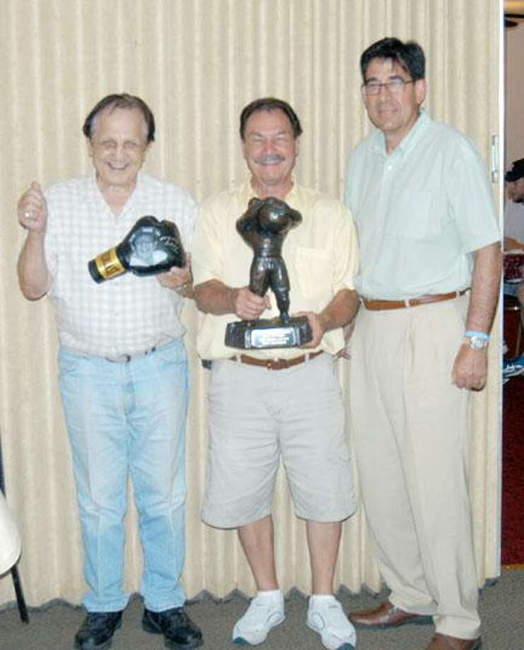 Dispatch Staff Photo by KYLE MENNIGTony Graziano, left, holds his Bare Knuckle Boxing Hall of Fame induction glove as Billy Backus, center, holds the induction statue with Ed Brophy, executive director of the International Boxing Hall of Fame, at GrazianoÕs in Canastota Monday, July 30, 2012.