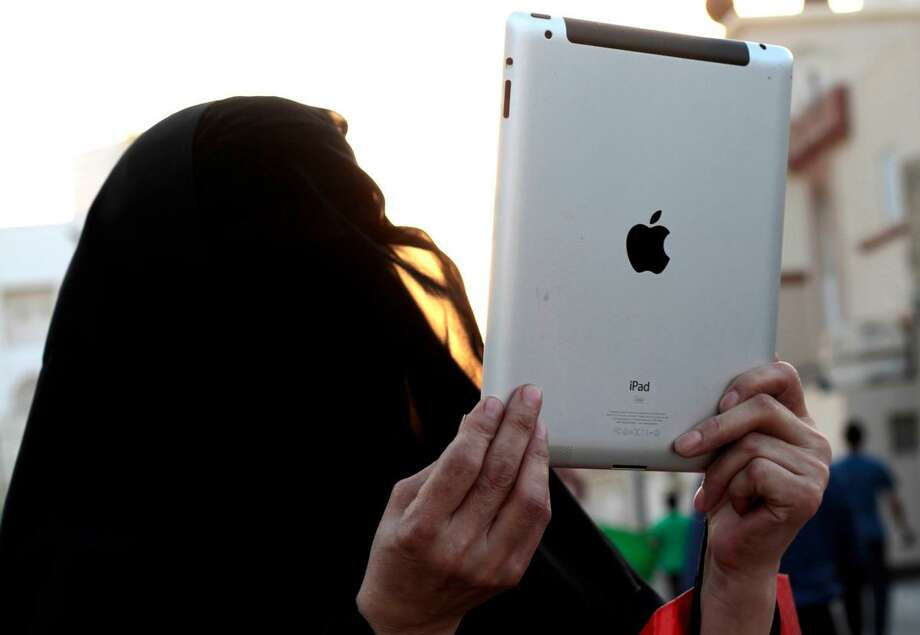 A Bahraini woman uses an iPad to photograph a rally in Diraz, Bahrain, on Thursday, Sept. 27, 2012, against a film made in the United States that denigrates Islam's founding Prophet Muhammad. A few hundred people participated in the march, chanting slogans against the United States and Israel. (AP Photo/Hasan Jamali) Photo: ASSOCIATED PRESS / AP2012