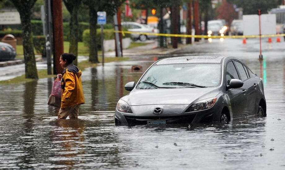 West Haven-- A woman leaves her car after it stalled in the water under the railroad bridge along Campbell Avenue in West Haven during heavy rains Friday Afternoon.  Photo Peter Casolino/New Haven Register