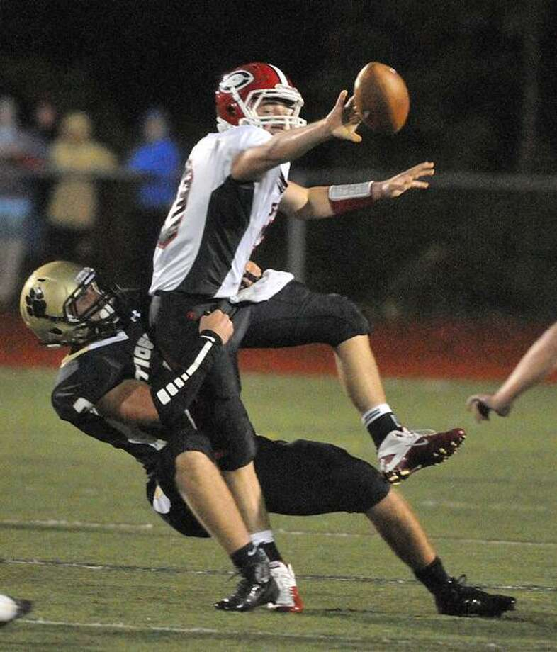 Madison-- Cheshire QB Vincent Sansone tries to pitch the ball at the last minute as Hand's Peter Gerson makes the sack in the first quarter.  Photo Peter Casolino/New Haven Register 09/28/12