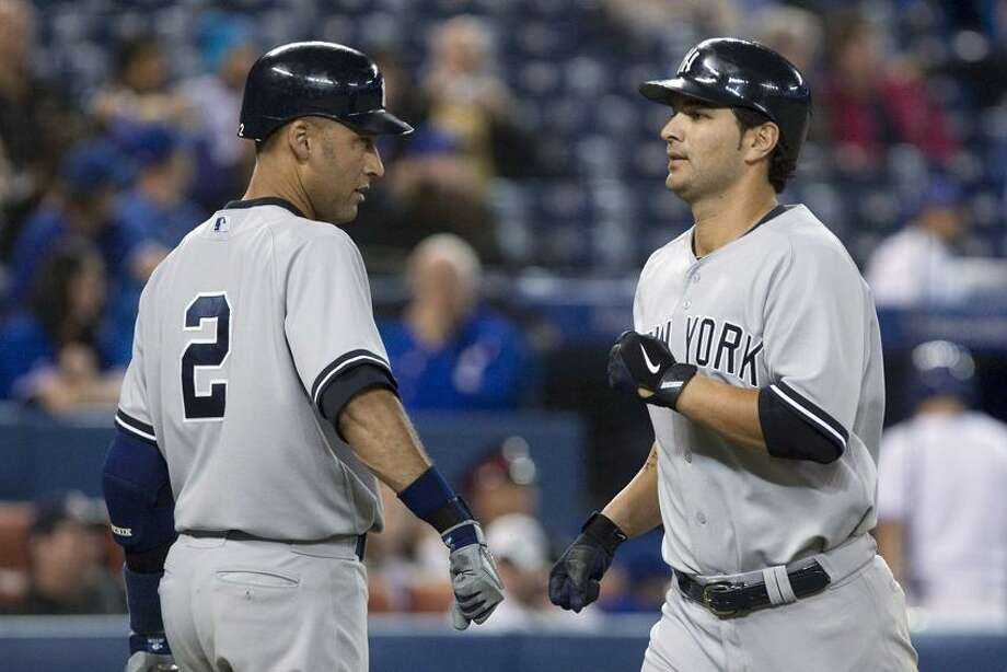 New York Yankees' Eric Chavez, right, is congratulated by Derek Jeter after hitting a home run against the Toronto Blue Jays during the ninth inning of a baseball game in Toronto on Friday, Sept. 28, 2012. (AP Photo/The Canadian Press, Chris Young) Photo: AP / The Canadian Press