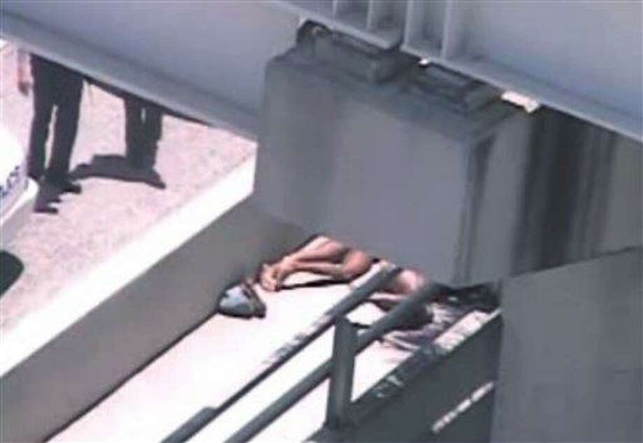 In this image taken from video, Miami police officers stand watch near a naked man, legs showing, second from right, who was shot dead by a police officer when he refused to stop chewing on the face of the naked man next to him, partially obscured by a railing, on the MacArthur Causeway ramp onto Northeast 13th Street in Miami, Saturday. The victim was taken to a nearby hospital. Police say neither man's identity is known.  Associated Press Photo: AP / The Miami Herald