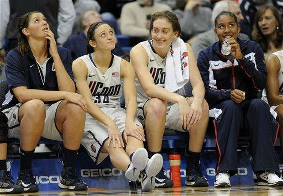 Connecticut's Stefanie Dolson, left, Kelly Faris, second from left, Breanna Stewart, second from right and Kaleena Mosqueda-Lewis, right, react in the final minutes of the second half of a NCAA college basketball game in Hartford, Conn., Wednesday, Nov. 28, 2012. Connecticut won 101-41. (AP Photo/Jessica Hill) Photo: AP / FR125654 AP