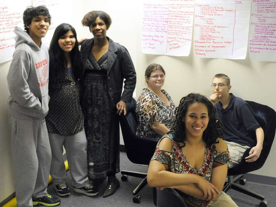 Left to right: Mark Ifill-Haney, Youth Unleashed student leader, 15, with his  sister Eryn Ifill,13, a probationary Youth Unleashed student leader and  his mother  Megan Ifill, Teach Our Children parent leader; Renee Wells, Teach Our Children parent leader with her son Kenneth Wells, Youth Unleashed student leader, 15, and Camelle Scott-Mujahid, Director of Teach Our Children & Youth Unleashed Wednesday, November 28, 2012  at the Teach Our Children office in New Haven. The Non-profit community activist organization Teach Our Children is meeting with the New Haven School district school on issues of bus safety and healthy food. Photo by Peter Hvizdak / New Haven Register Photo: New Haven Register / ©Peter Hvizdak /  New Haven Register
